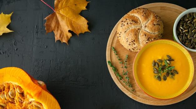 Sopa de abóbora caseira vegana de outono plana com sementes, ervas e pão, em um fundo preto