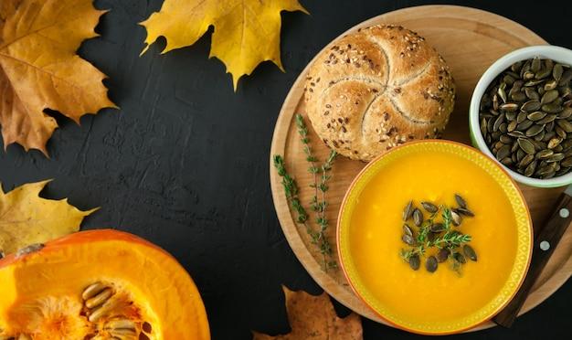 Sopa de abóbora caseira vegana de outono vista de cima com sementes, ervas e pão, em um fundo preto