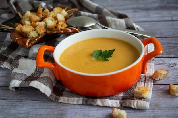 Sopa de abóbora cenoura creme em um prato laranja com biscoitos em uma toalha xadrez com fundo de madeira