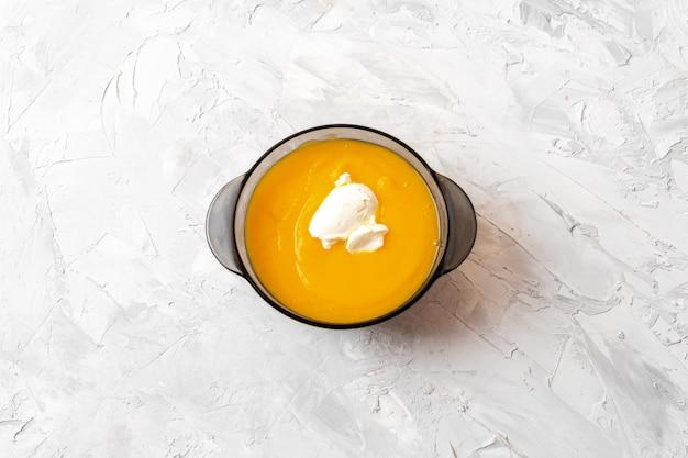 Sopa de abóbora com creme de leite na superfície de concreto cinza