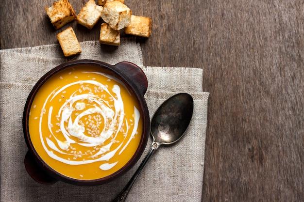 Sopa de abóbora com creme e sementes de gergelim com croutons em fundo de madeira
