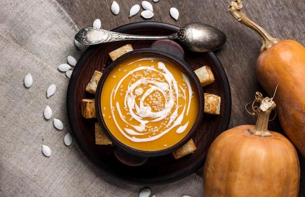 Sopa de abóbora com creme e sementes de gergelim em tigela de cerâmica marrom sobre superfície de madeira