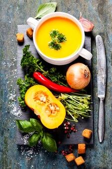 Sopa de abóbora com ingredientes frescos em tábua de madeira