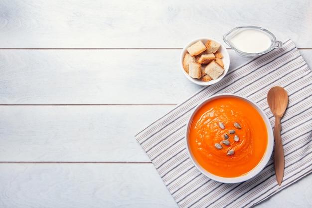Sopa de abóbora com purê de pão ralado, creme e sementes em um fundo branco de madeira. copie o espaço.