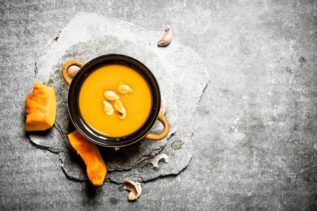 Sopa de abóbora com sementes na mesa de pedra