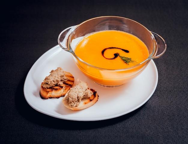 Sopa de abóbora e cenoura com creme e salsa na mesa escura