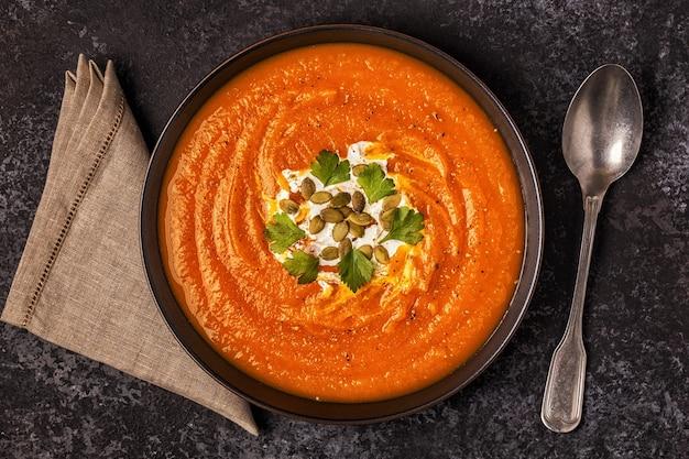Sopa de abóbora e cenoura com creme, sementes e salsa vista superior