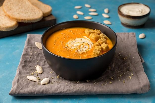 Sopa de abóbora e cenoura com croutons cremosos no guardanapo em uma tigela preta
