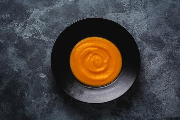 Sopa de abóbora em placa de cerâmica preta sobre fundo escuro de madeira. comida tradicional de outono. espaço da cópia da vista superior.