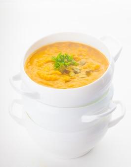 Sopa de abóbora em tigela branca sobre fundo branco