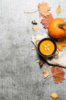 Sopa de abóbora estilo outono de uma abóbora madura na mesa de pedra