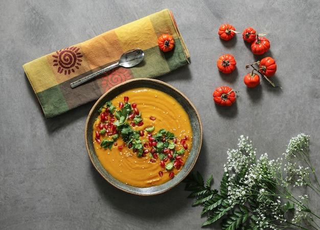 Sopa de abóbora fresca coberta com sementes de salsa e romã