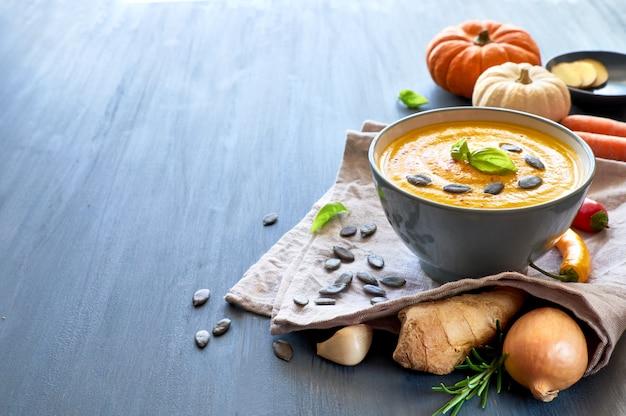 Sopa de abóbora picante com gengibre, cebola e alho, servida com manjericão, sementes de abóbora e pimenta seca