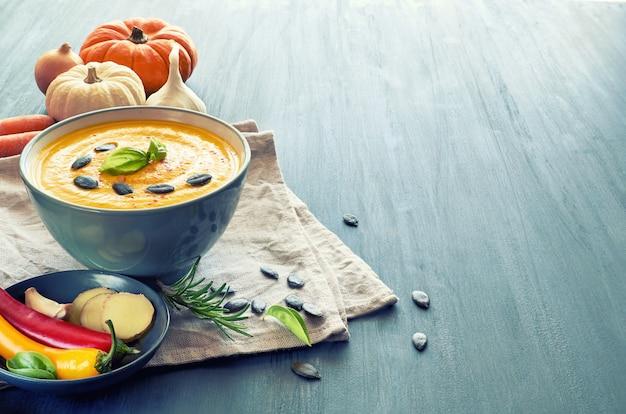 Sopa de abóbora picante servida com manjericão, sementes de abóbora e pimentão seco