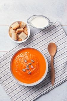 Sopa de abóbora purê com pão ralado, creme e sementes na toalha, fundo branco de madeira.