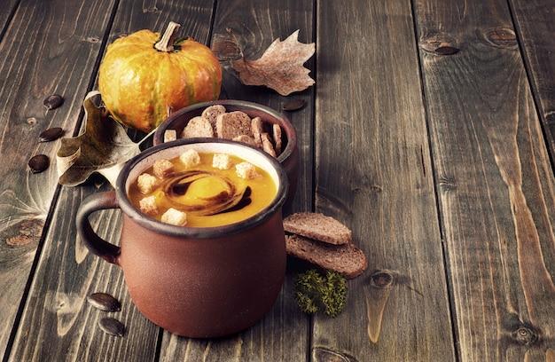 Sopa de abóbora saboroso na velha caneca de esmalte na mesa de madeira rústica