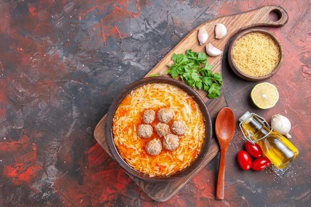 Sopa de almôndegas com macarrão a bordo de massas cruas, limão, verde, óleo, garrafa e colher, na mesa escura