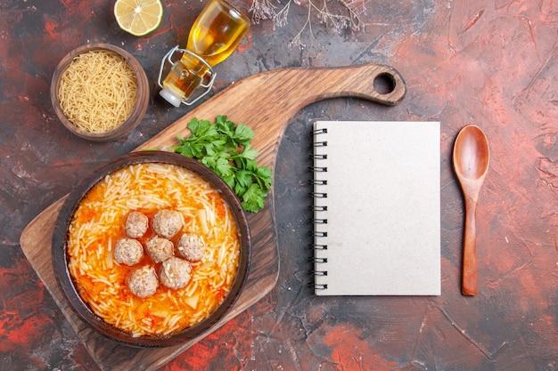 Sopa de almôndegas com macarrão a bordo de massas crus, folhas de limão e colher de caderno em fundo escuro.