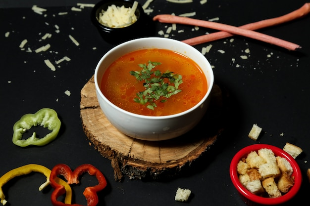 Sopa de arroz em tigela bolachas cebola pimentão vista lateral