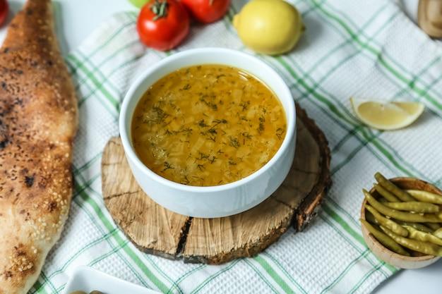 Sopa de arroz na tigela na placa de madeira com legumes