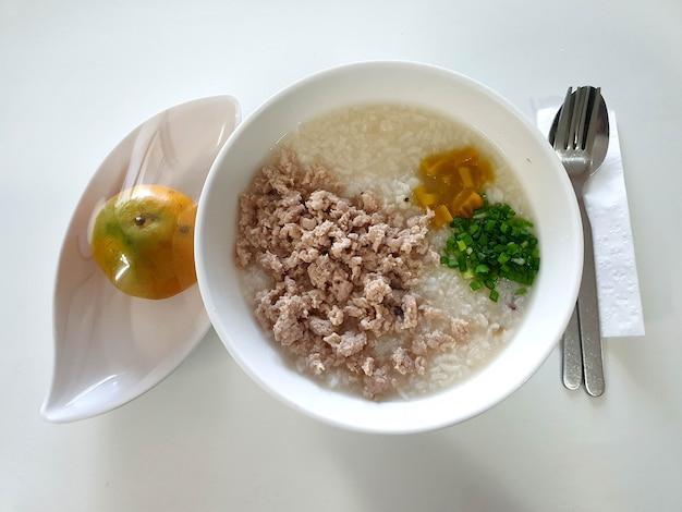 Sopa de arroz tailandesa com carne de porco com laranja na mesa uma popular sopa de arroz no café da manhã na tailândia