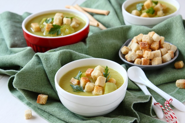 Sopa de batata-doce cremosa com croutons e salsa em tigela branca