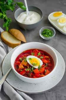 Sopa de beterraba com legumes, ovo cozido e creme de leite