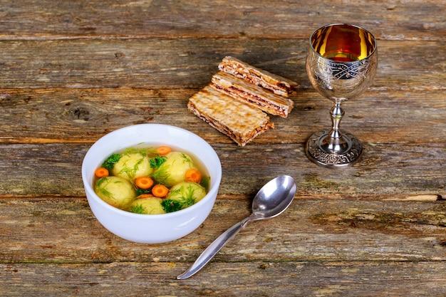 Sopa de bola de matzo caseiro quente em uma tigela de vinho de páscoa e matzah