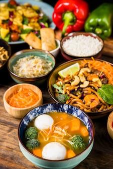Sopa de bola de peixe e tigela de macarrão na mesa de madeira