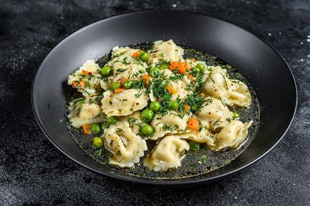 Sopa de bolinhos com macarrão ravioli em uma tigela com verduras