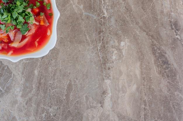 Sopa de borsch russa com enfeite de coentro no mármore.