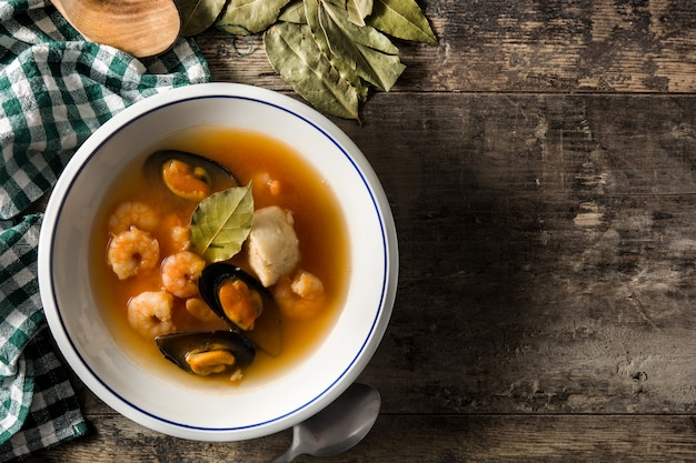 Sopa de bouillabaisse francês na mesa de madeira.
