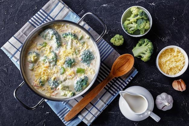 Sopa de brócolis e queijo cheddar em uma panela em uma mesa de concreto com queijo ralado e creme de leite fresco na mesa, vista horizontal de cima, camada plana