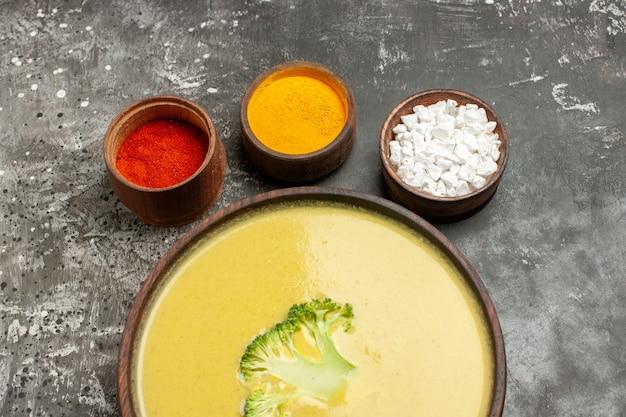 Sopa de brócolis em uma tigela marrom e temperos diferentes na mesa cinza