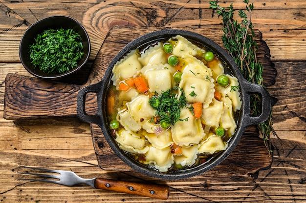 Sopa de caldo com massa de ravióli em uma panela