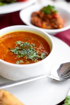 Sopa de caldo de galinha de vista lateral com pão em uma mesa servida