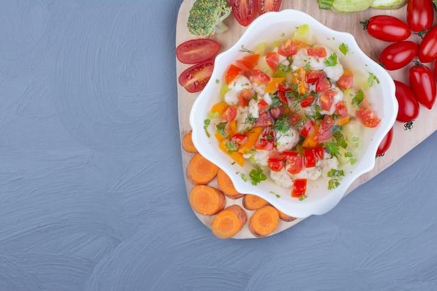 Sopa de caldo de legumes em uma tigela branca com alimentos picados
