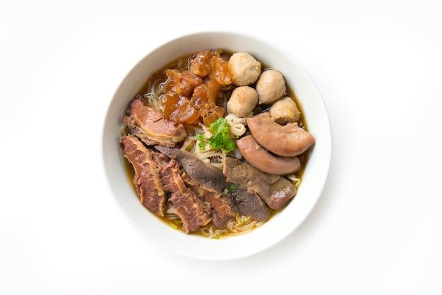 Sopa de carne assada clara com macarrão (kuay taiw nuae toon) em tigela vista superior em fundo branco