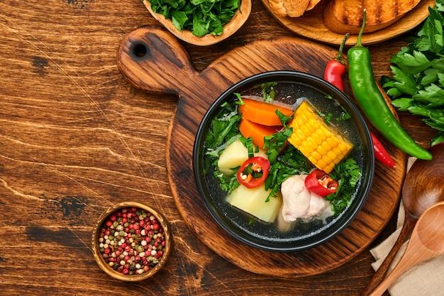 Sopa de carne chilena com pampkin, milho, coentro fresco e batatas no fundo da velha mesa de madeira. cazuela. comida latino-americana.