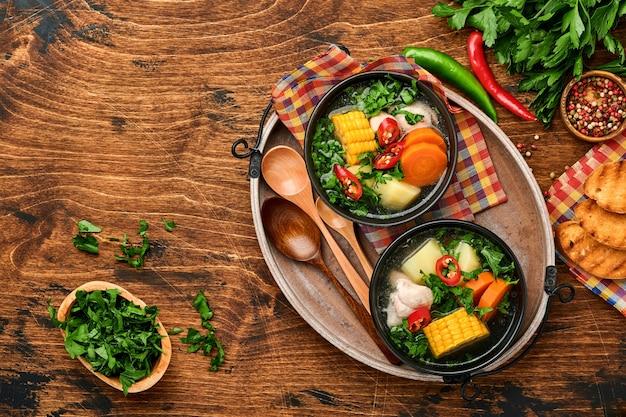 Sopa de carne chilena com pampkin, milho, coentro fresco e batatas no fundo da velha mesa de madeira. cazuela. comida latino-americana. Foto Premium