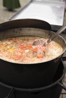 Sopa de carne com ervas e temperos ferve no fogo em uma panela grande