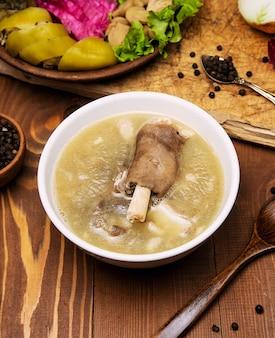 Sopa de carne de borrego com um pedaço de carne, molho de tomate e cebola, sumakh.
