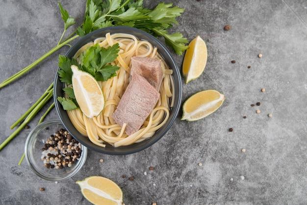 Sopa de carne e macarrão com fatias de limão