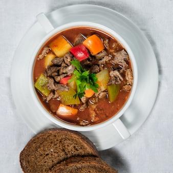Sopa de carne kharcho com legumes em um prato com pão à parte em um fundo branco