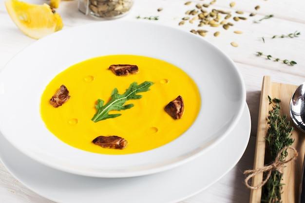 Sopa de cenoura ao curry com cogumelos e ervas frescas.