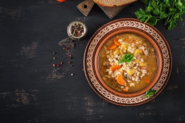 Sopa de cevada com cenoura, tomate, aipo e carne em uma mesa escura