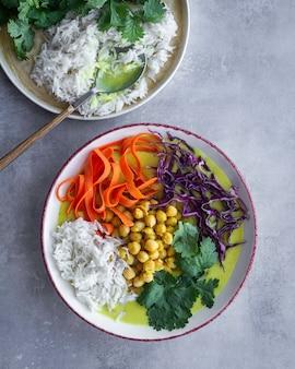 Sopa de coco e curry verde com grão de bico, arroz basmati e legumes. comida caseira.