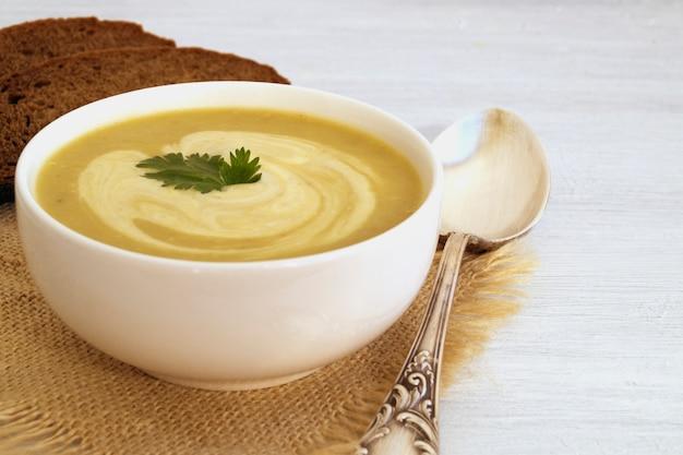 Sopa de cogumelo caseiro da dieta em um fundo claro.