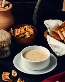 Sopa de cogumelos com pão na mesa