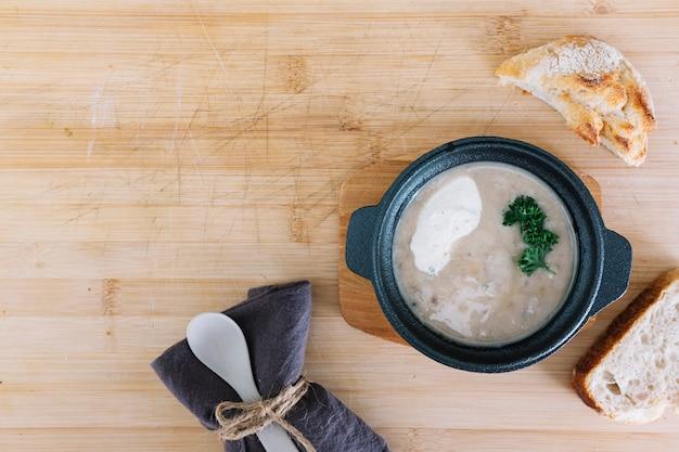 Sopa de cogumelos com pão; toalha de mesa e colher em pano de fundo de madeira
